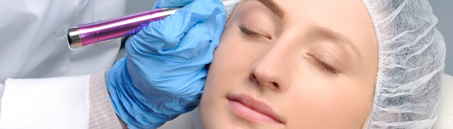 Microblading eyebrows. Cosmetologist making permanent makeup. Attractive woman getting facial care and tattoo at beauty salon