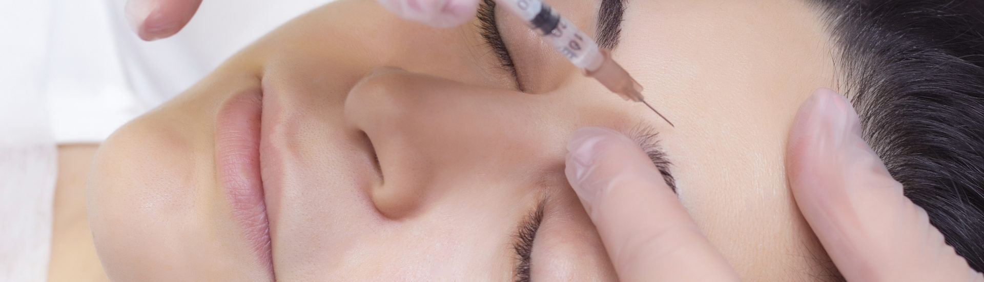 Close-up of a beautician injecting into forehead wrinkles. She holds a syringe. Cosmetics injected womans face